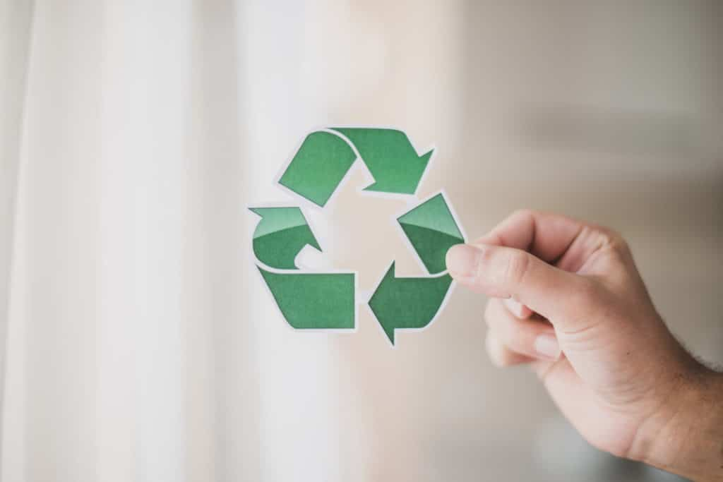man s hand showing recycle icon